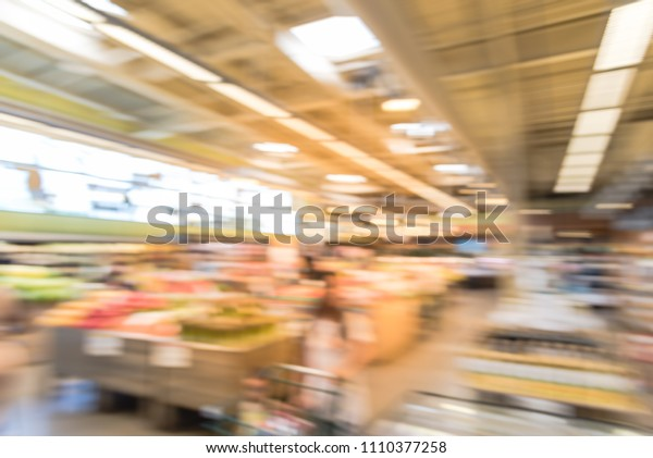 Blurred abstract people shopping for fresh fruits and vegetables at grocery store. Organic and locally grown produces on display in Allen, Texas, USA. Healthy food abstract background in supermarket
