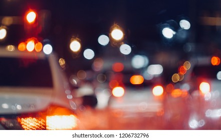 blurred abstract of traffic jam on street in city through front car window