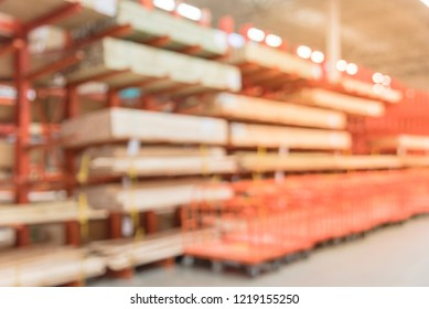 Blurred abstract wide selection of pressure treated lumber, studs, wood trim and row of flatbed carts. Defocused lumber section of hardware store in America.