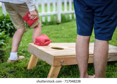 blurred action of two guys playing cornhole game in backyard