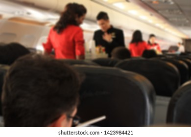 Blurred air hostess working in Airplane interior, have noise, have blur.