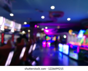 blurred arcade machine game for children game play  in department store. Playground with colorful neon lights and bokeh light. Colorful absract background.