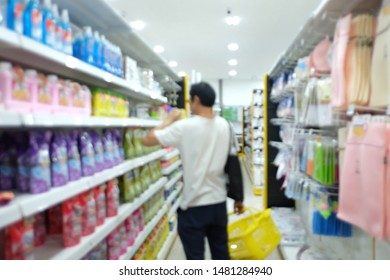 Blurred asian male standing in superstore aisle with a yellow basket and try to choose a goods from a shelf