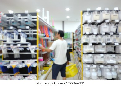 Blurred asian male standing in superstore aisle with a yellow basket and try to choose a craftsman tool from a shelf