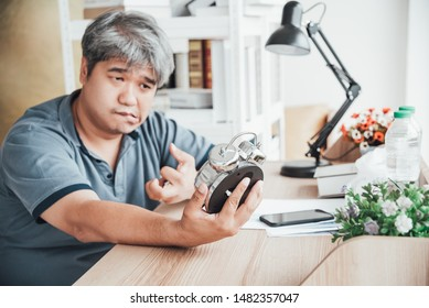 Blurred of Asian man, He is patient from neurological diseases, or hemiplegia having a facial palsy and kinking fingers, He is looking at the alarm clock in his hand, to health paralysis concept.