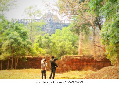 blurred asian man with woman travel and photography at archaeological site, siemreap combodia.