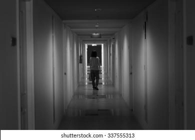 Blurred Asian woman walking in corridor hotel.