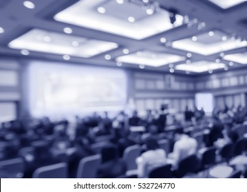 Blurred audience  in auditorium  or  hall with monitor, blue color