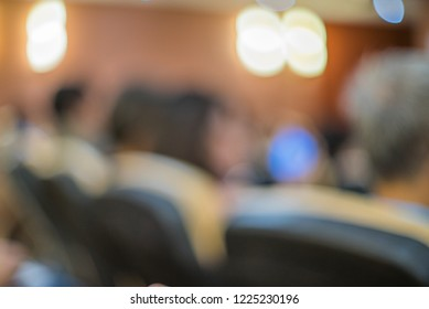 Blurred audience oblique rear view, group of people sitting in classroom, conference, seminar meeting room, chair row with bokeh light background. Education and public hearing concept. Orange tone.