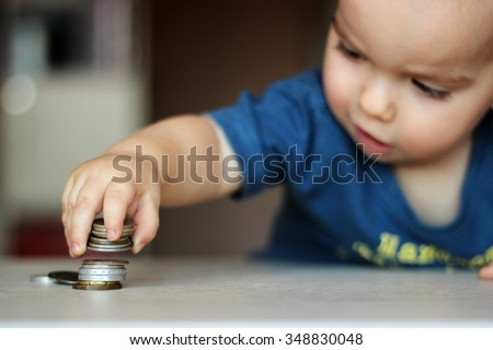 Blurred baby boy putting some coins into other ones, focus on the coins, indoor financial concept