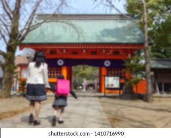 blurred back of Japanese primary student and mother walking into the gate of temple to pray for first day of school entrance ceremony.