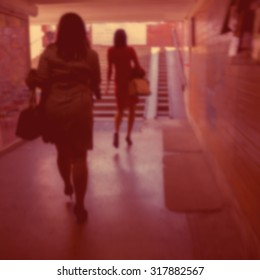 blurred backgound, silhouettes of a woman walking in the underpass