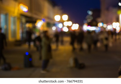 Blurred background. Abstract background of blurred lights and peoples on the street with bokeh effect. Defocused street abstract texture for design.