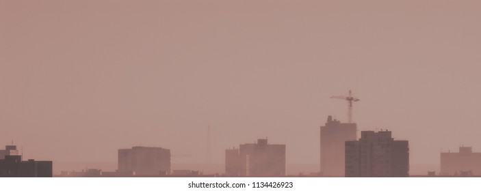 Blurred background, the appearance of urban buildings and construction in the morning haze. Web banner for design.