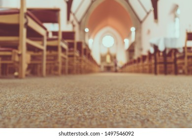 Blurred background of a beautiful illuminated church aisle with focus on floor carpet for spiritual holy ground prayer Mass concept. Church interior with wooden church benches of a Christian church