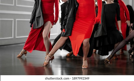 Blurred background  of beautiful  woman legs dancing tango wearing black and red dresses, unrecognizable