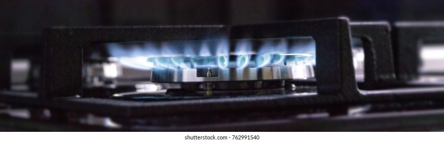 Blurred background. Blue gas flame on the gas stove
