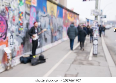 Blurred background of busker playing at Berlin Wall