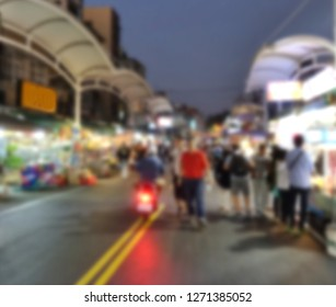 Blurred background of a busy evening market with stalls and restaurants