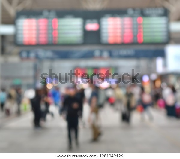 A blurred background of a busy transportation terminal such as a bus or train station