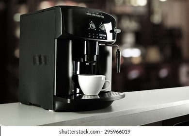blurred background of cafe and coffee machine with white cup and space for you