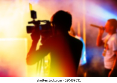 Blurred Background, Cameraman is Videotaping the Concert.