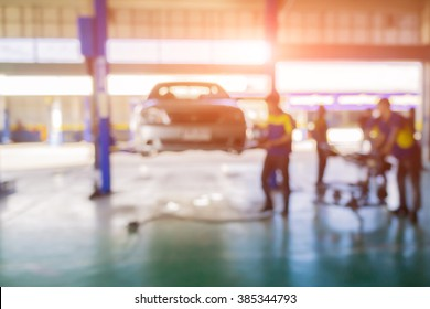 Blurred background of car technician repairing the car in garage,mechanics fixing car in a workshop background,car suspension detail of lifted automobile at repair service station,vintage color.
