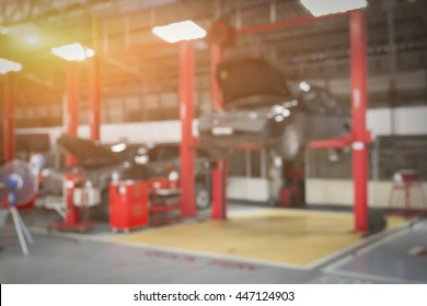 Blurred background of car technician repairing the car in garage,mechanics fixing machine in a workshop,auto-car suspension detail of lifted automobile at repair service station,vintage color.