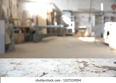 Blurred background of carpentry workshop. Machinery background and table scratched stained table top. Copy space.