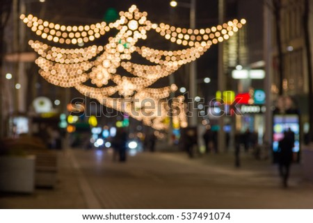 blurred background of christmas street lights with people silhouettes in vienna austria