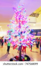 Blurred background of a christmas tree with beautiful lights in a shopping center