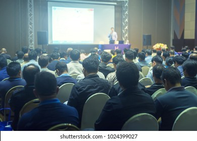 Blurred background of Clouds listening to the Speakers on the stage with Rear view of Audience in the conference hall or seminar meeting, business and education about investment concept