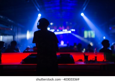 Blurred background : Club, disco DJ playing and mixing music for crowd of happy people. Nightlife, concert lights, flares