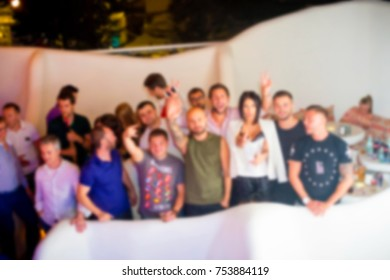 Blurred for background. club party. People smiling and posing on cam during concert in night club party. Man and woman have fun at club. Boy and girl at night club party
