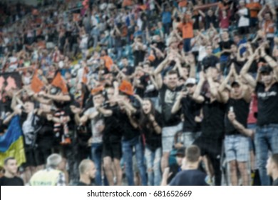 Blurred background of crazy football fans at the stadium. Fanatical fans in stands during game of rivals. Fans in stands rejoice, shout and fluttering flag. People are looking at stadium. Strong blur