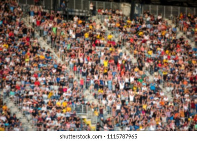 Blurred background of crowd of people at football match in the stadium