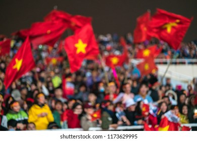 Blurred background of crowd of Vietnamese football fans at My Dinh stadium. Supporter with red clothes raising flags.