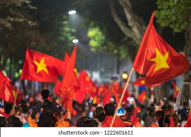 Blurred background of crowd of Vietnamese football fans down the street to celebrate the win after soccer, with a lot of Vietnamese flags raising high
