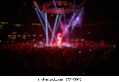 Blurred background of crowded dance floor in nightclub.Big live music show in the club.People have fun on popular dj concert.Music fans burn red fire torch on dancefloor.Dangerous flammable show