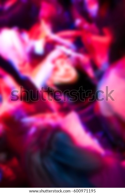 Blurred background with dancing party people dancing on dance floor.Crowded night club,young adult people have fun at night life entertainment event