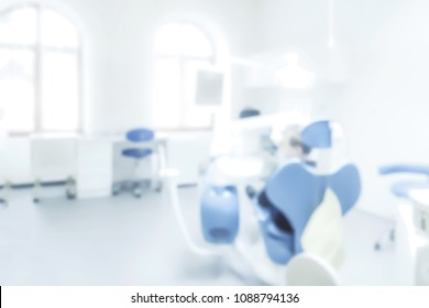 Blurred background of a dentist office with a patient on a chair ( copy space)