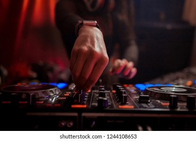 Blurred background with dj girl playing music and scratching tracks on professional dj midi controller.Modern disc jockey digital audio equipment for concerts or house party event.Stage lighting