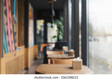 Blurred background of a empty cafe with wooden tables and chairs