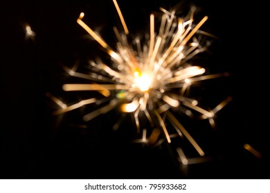 Blurred background. Festive sparkling light with bright sparks close up. Bengal flame on black background.
