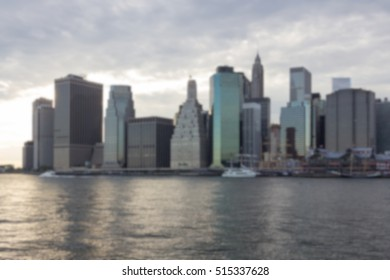 Blurred background of Financial District skyline in downtown Manhattan set against evening clouds.