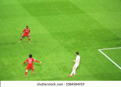 Blurred background of football player playing and running with the ball in match day on beautiful green field with sport light at the stadium.Sports,Athlete,People Concept.mercy side,Anfield,Liverpool