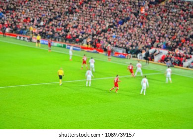 Blurred background of football player playing and running with the ball in match day on beautiful green field with fans and sport light at the stadium.Mercy Side,Anfield,Liverpool.UK