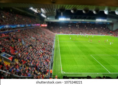 Blurred background of football players playing and soccer fans in match day on beautiful green field with sport light at the stadium.Sports,Athlete,People Concept.Anfield,Liverpool,UK