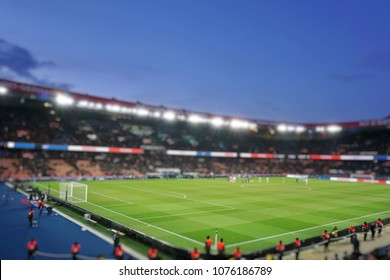 Blurred background of football players playing and soccer fans in match day on beautiful green field with sport light at the stadium.Sports,Athlete,People Concept.Paris saint-germain.France.