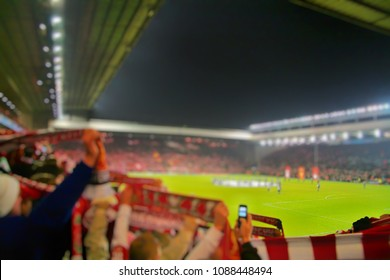 Blurred background of football players playing and soccer fans in match day on beautiful green field with sport light at the stadium.Sports,Athlete,People Concept.Anfield,Liverpool.UK